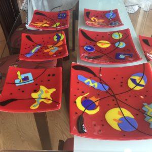 Najia Art Glass Plates on table, each red background with multi coloured patterns